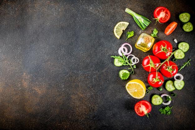 Mesa de cocina, ingredientes para ensaladas frescas, cocina italiana: tomates, aceite de oliva, limón, pepinos, rúcula, perejil, cebolla, vista de mesa oxidada oscura