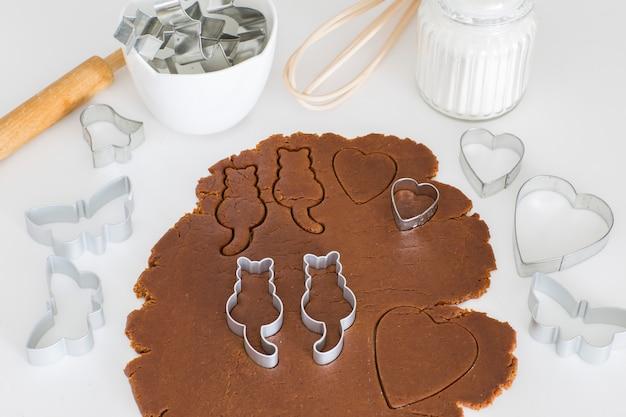 En la mesa de la cocina masa de jengibre enrollada, en ella cortadores de galletas en forma de gatos - día mundial del gato