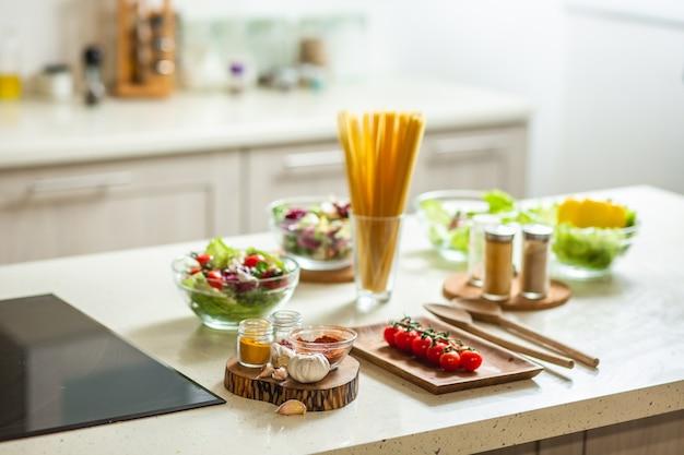 Mesa de cocina de piedra blanca con cuencos de ensaladas, especias y verduras