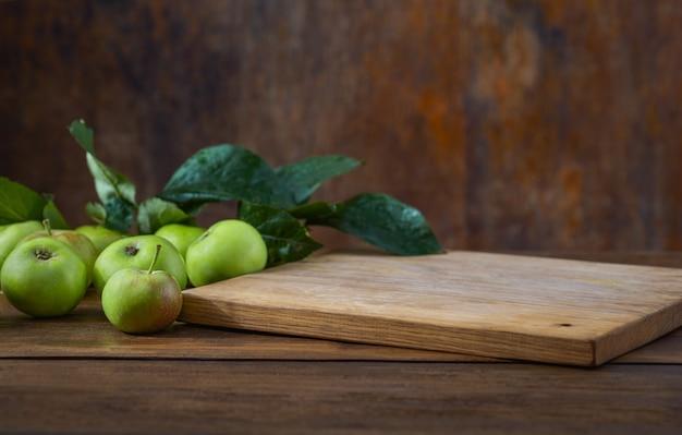 Mesa de cocina con tabla de cortar vacía y manzanas verdes