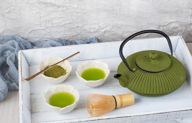 En la mesa coincide con el té en los tazones para beber, batidor de té, cuchara, tetera - ceremonia del té