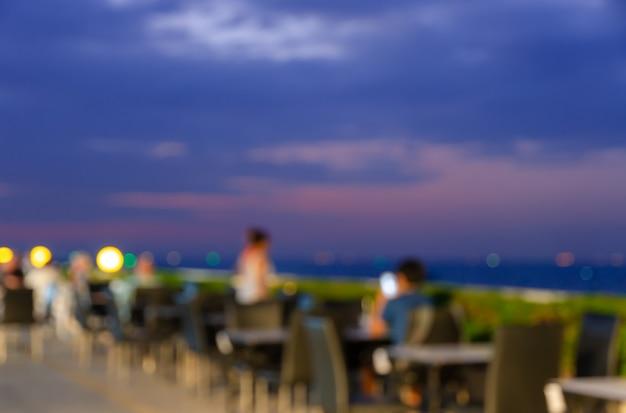 Mesa de comedor borrosa restaurante junto a la piscina en la azotea con hermosa vista al mar en la escena del crepúsculo