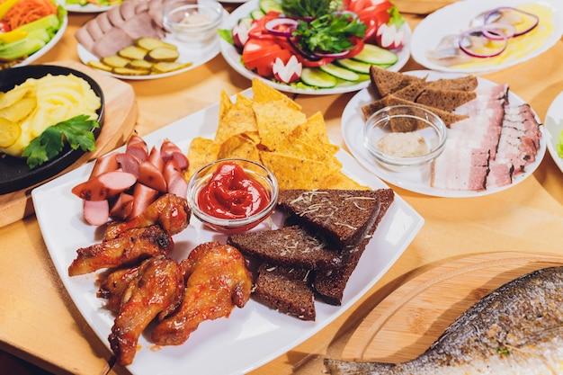 Mesa de comedor con gran variedad de aperitivos y ensaladas. salmón, aceitunas, vino, verduras, tostadas de pescado a la parrilla.