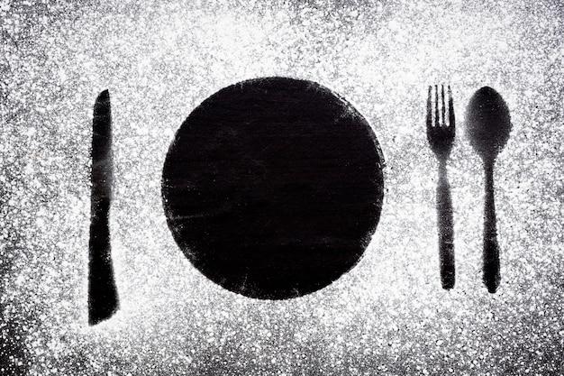 Mesa de comedor harina blanca rociada en el plato de la mesa una cuchara y un cuchillo