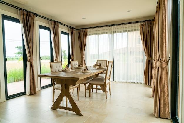 Mesa de comedor de madera en una habitación con cortina y ventana.