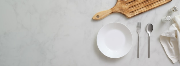 Mesa de comedor de mármol con plato blanco, cubiertos, bandeja de madera y espacio de copia