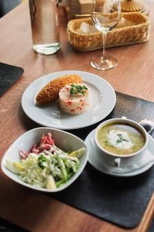 Mesa de comedor: un plato de sopa, risotto con chuleta y ensalada de verduras vista lateral