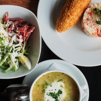Mesa de comedor: un plato de sopa, risotto con chuleta y ensalada de verduras vista superior