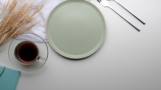 Mesa de comedor con plato turquesa, cubiertos, taza de té, servilleta, espacio de copia y trigo dorado decorado en la mesa