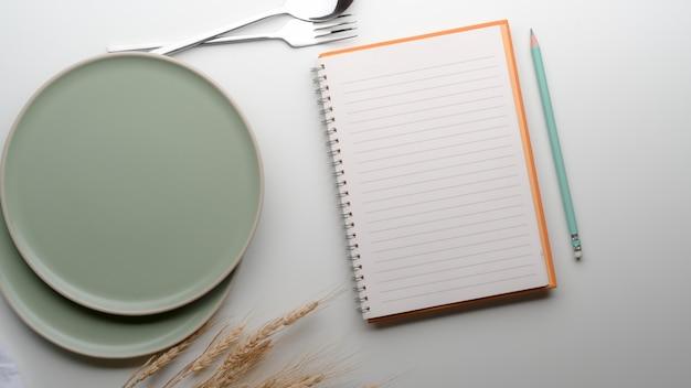 Mesa de comedor con platos de cerámica turquesa, cubiertos, cuaderno en blanco, lápiz y trigo dorado decorados en la mesa