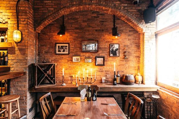 Mesa de comedor de restaurante italiano decorada con ladrillo y marcos de fotos en luz cálida.