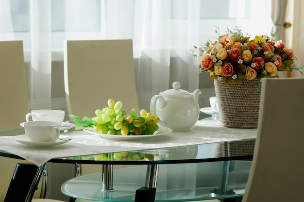 Mesa de comedor con vajilla para té, uvas, flores.