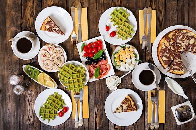 Mesa de comida de desayuno. brunch festivo, variedad de comidas con waffles de espinacas, salmón, queso, aceitunas, rollitos de pollo y tarta de queso. vista superior. lay flat