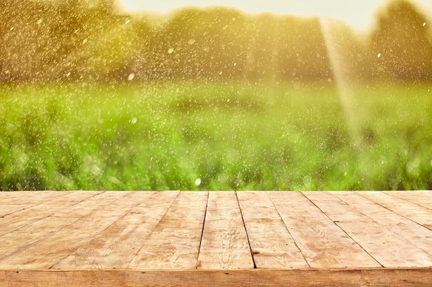 Mesa cubierta de madera vacía con fondo de follaje bokeh. listo para montaje de exhibición de productos. Foto Premium