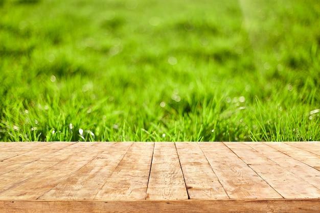 Mesa cubierta de madera vacía con fondo de follaje bokeh. listo para montaje de exhibición de productos.