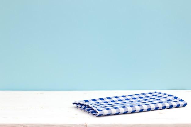 Mesa cubierta de madera vacía con mantel sobre fondo azul pastel