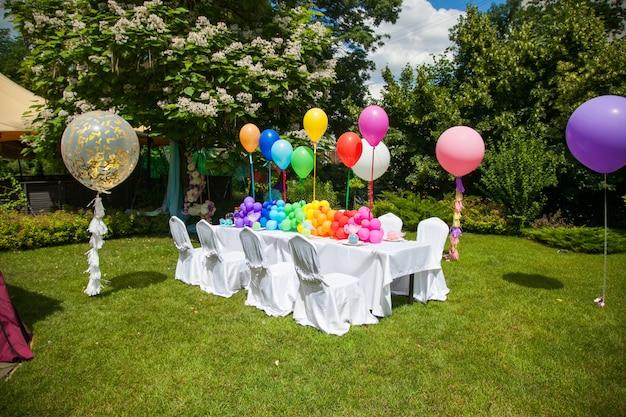 Mesa de cumpleaños con globos arcoiris. vacaciones de verano en el parque.