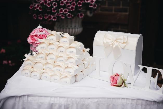 Mesa para dar a los recién casados. cajas de dulces de boda, blancas. regalos para invitados. decoración de boda, estilo,