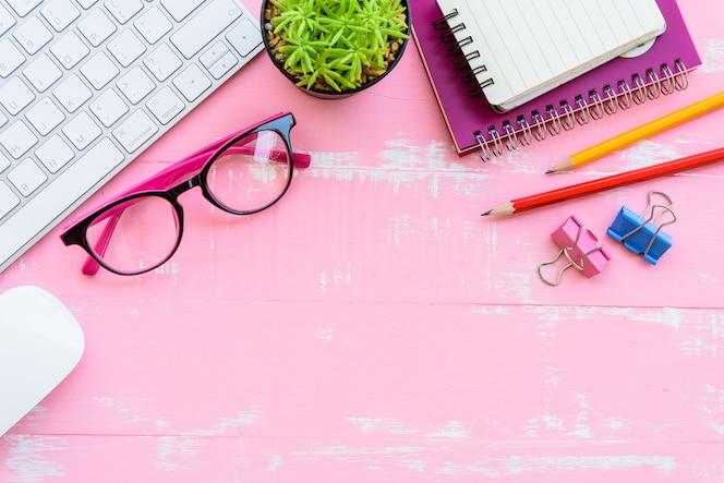 Mesa de oficina con accesorios de espacio de trabajo y oficina en fondo de madera rosa.