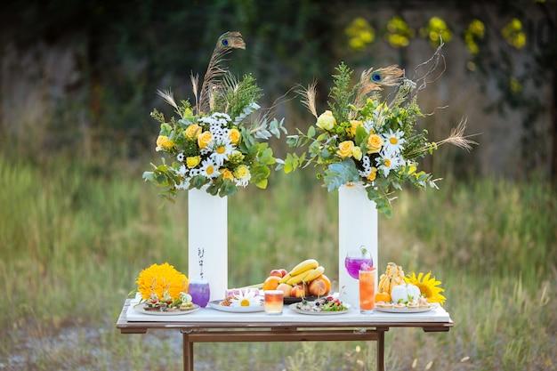Mesa decorada para un buffet de verano con flores, cócteles y aperitivos en una mesa de madera blanca.