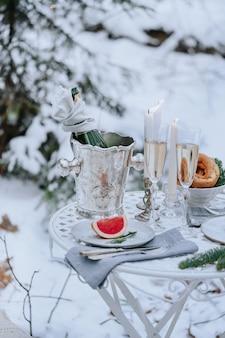 Mesa decorada para una cena romántica con velas, vino espumoso y fruta en el bosque de invierno.