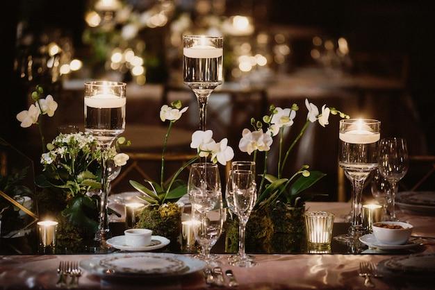 Mesa decorada con orquídeas y velas, vasos a la luz.