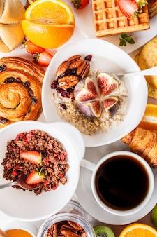 Mesa de desayuno con avena, gofres, cruasanes y frutas.