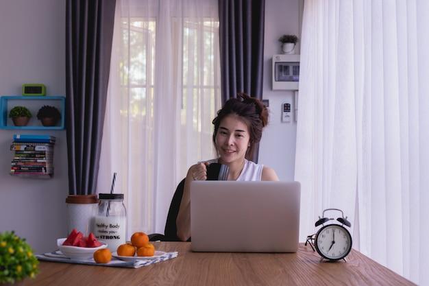 Mesa de desayuno con el café asiático joven del dink de la mujer, trabajadora por mañana.