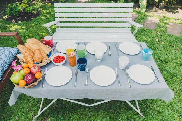 Mesa de desayuno con comida en el jardín.