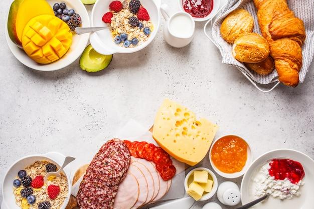 Mesa de desayuno continental con croissants, mermelada, jamón, queso, mantequilla, granola y fruta, copia espacio.
