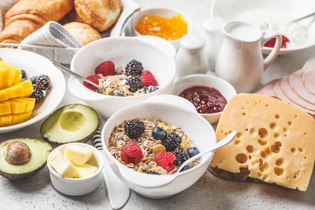 Mesa de desayuno continental con croissants, mermelada, jamón, queso, mantequilla, granola y fruta.