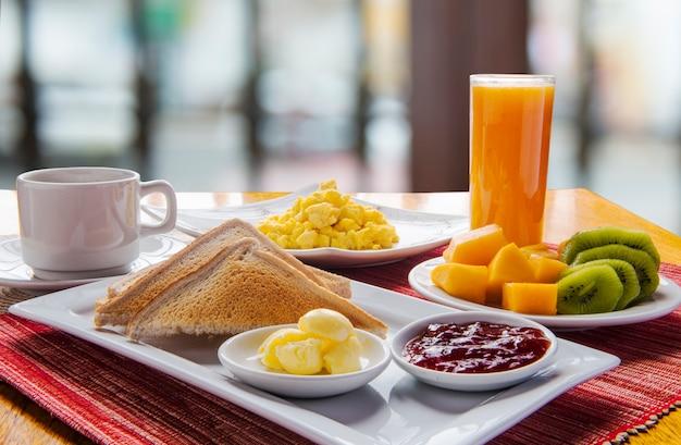 Mesa de desayuno continental fresca y luminosa con plato de frutas.