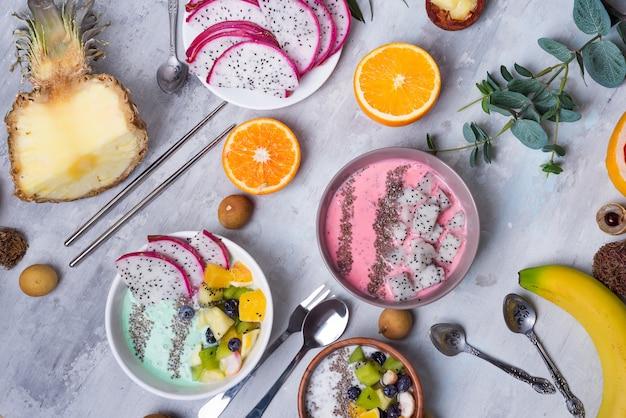 Mesa de desayuno con cuencos de yogurt acai y frutas tropicales frescas sobre un fondo de piedra gris con hojas de eucalipto, plano