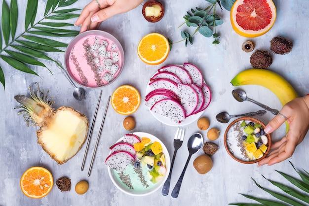 Mesa de desayuno con cuencos de yogurt acai y frutas tropicales frescas sobre un fondo de piedra gris con mano de wooman y hojas de palma, endecha plana