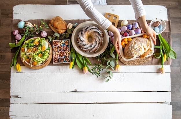 Mesa de desayuno o brunch llena de ingredientes saludables para una deliciosa comida de pascua con amigos y familiares alrededor de la mesa.