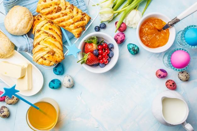 Mesa de desayuno de pascua. huevos de colores, bollos, zumo y mermelada. fondo azul, vista desde arriba, marco de alimentos.