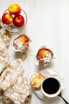 Mesa de desayuno con pasteles, café y frutas.