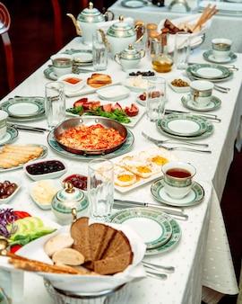 Mesa de desayuno con plato de huevos huevos revueltos panes salchichas queso y mermeladas
