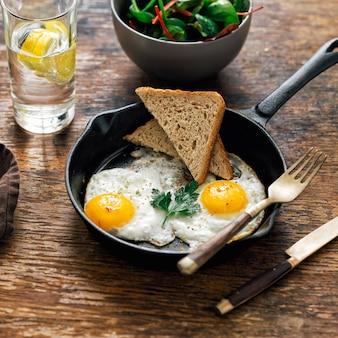 Mesa de desayuno pollo frito huevos pan ensalada limón agua
