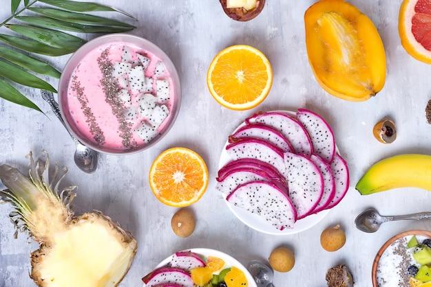 Mesa de desayuno con los tazones de fuente del smoothie de la fresa del yogur y las frutas tropicales frescas en un fondo de piedra gris. acai bowl de bayas silvestres y frutas smoothie bowl, plano
