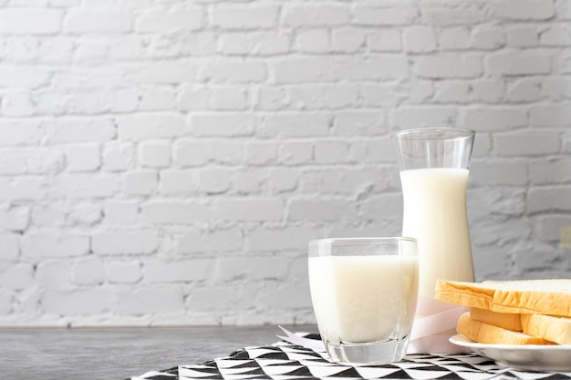 Mesa de desayuno con vaso de leche, jarra de leche.