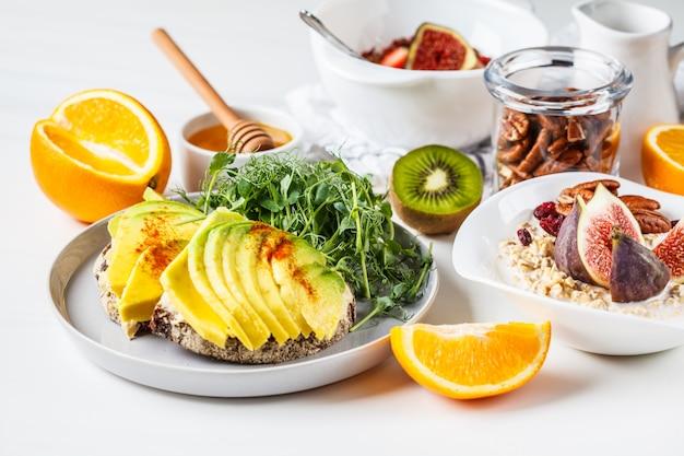 Mesa de desayuno vegana con tostadas de aguacate, avena, fruta, en blanco
