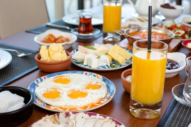 Una mesa de desayuno de vista frontal con huevos, bollos, queso y jugo fresco en el restaurante durante el desayuno.