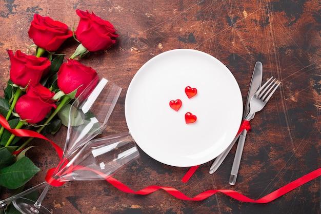Mesa del día de san valentín con plato vacío, rosas rojas y copas de champán sobre fondo de madera. vista superior. tarjeta de felicitación de san valentín