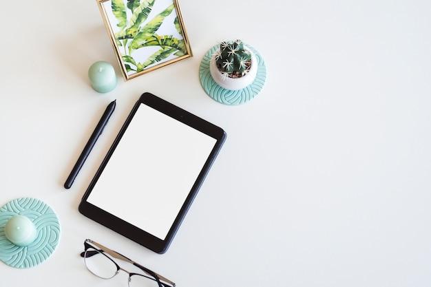Mesa con dispositivo móvil cerca de marco de fotos, cactus, pluma y anteojos