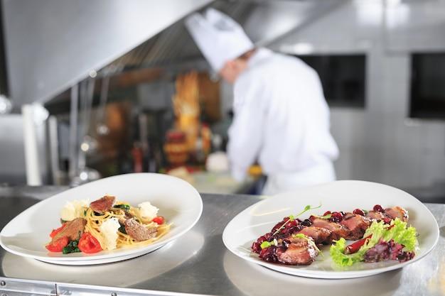 La mesa de distribución en la cocina del restaurante. el chef prepara una comida en el fondo de los platos terminados.