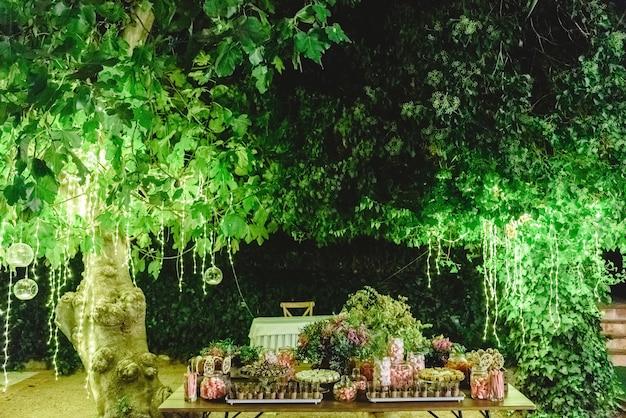 Mesa con dulces postres en un jardín por la noche.