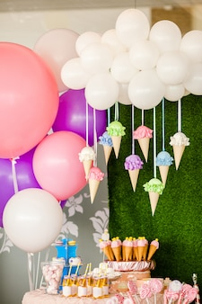 Mesa con dulces y postres, nubes de globos y helados y muchos globos de colores y grandes juguetes de caramelo