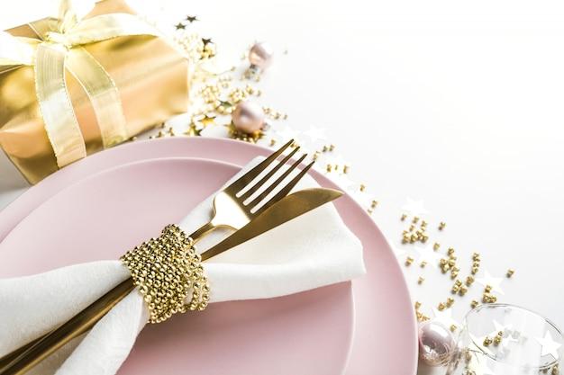 Mesa de elegancia navideña con vajilla rosa, cubiertos de oro sobre blanco. vista superior. cena de navidad.