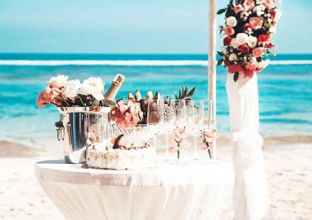 Mesa elegante de boda con frutas tropicales y pastel en la playa